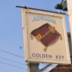 Pub sign for the Golden Key in Suffolk, Old fashioned key on velvet cushion.