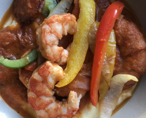 Illustration of Virginia's Shrimp and Grits with three cooked shrimp, sliced sausage, red, yellow and green sliced peppers.