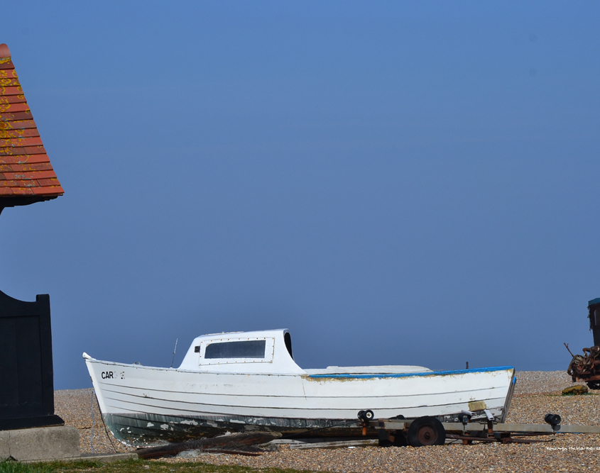 Heritage fishing boat on a trailer on a beach, blue skies and red tile roof