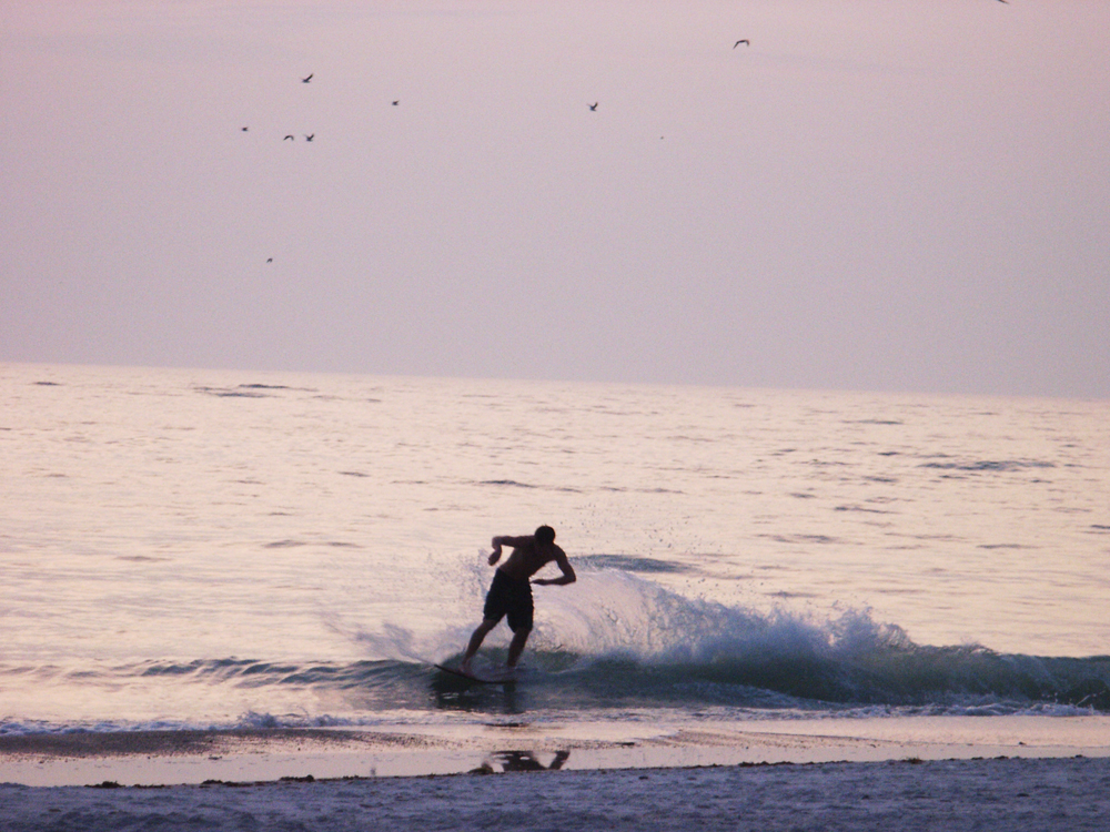 Boy skimming the shallow waves on a boogie board, with a lavender colored sky at sunset.