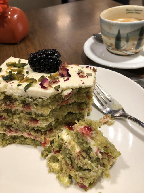 Pistachio cake - green layered cake with cream cheese frosting and a black berry on top