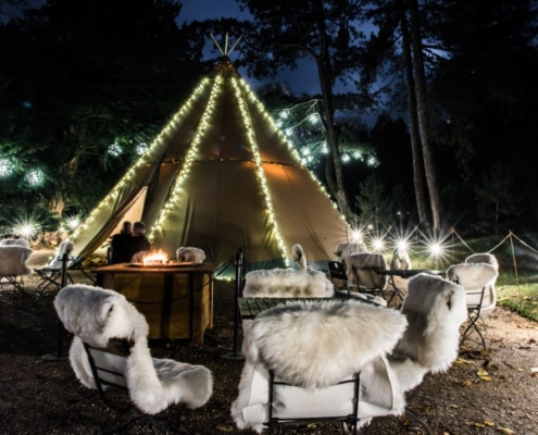 Wigwam with Christmas lights and sheepskin covered seats, wigwam, waddesdon manor, national trust, christmas 2019, christmas lights, woodland cafe